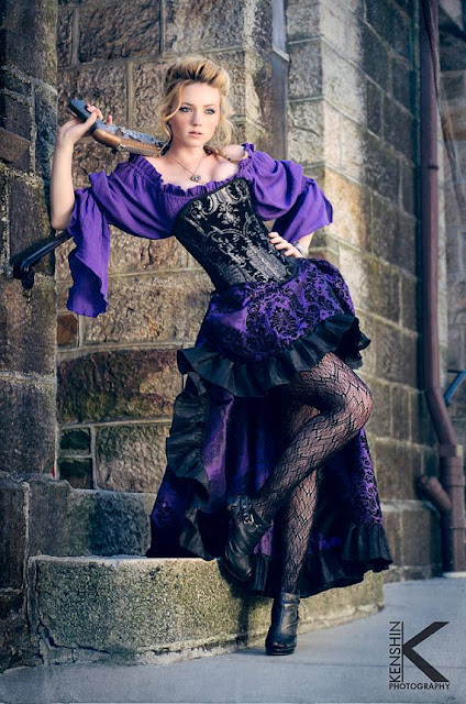 Woman's steampunk showgirl costume, or steampunk burlesque dancer cosplay. Purple skirt and blouse, black corset and boots.