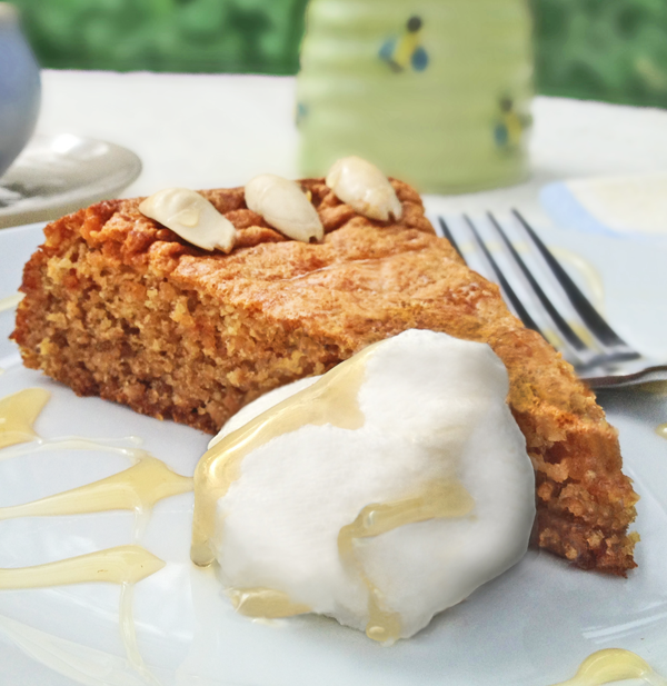 Image of a slice of Honey Almond Cake on a white plate with whipped cream.