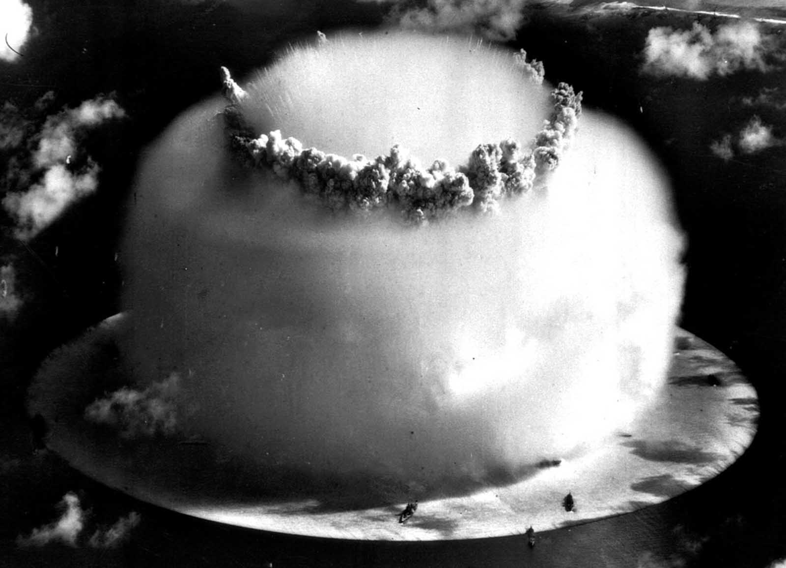 A huge mushroom cloud rises above Bikini Atoll in the Marshall Islands on July 25, 1946, following an atomic test blast, part of the U.S. military's Operation Crossroads. The dark spots in the foreground are ships that were placed near the blast site to test what an atomic bomb would do to a fleet of warships.