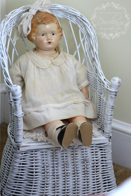 Antique doll on a child's wicker potty chair.