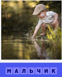 маленький мальчик в кепке около воды, пробует рукой воду