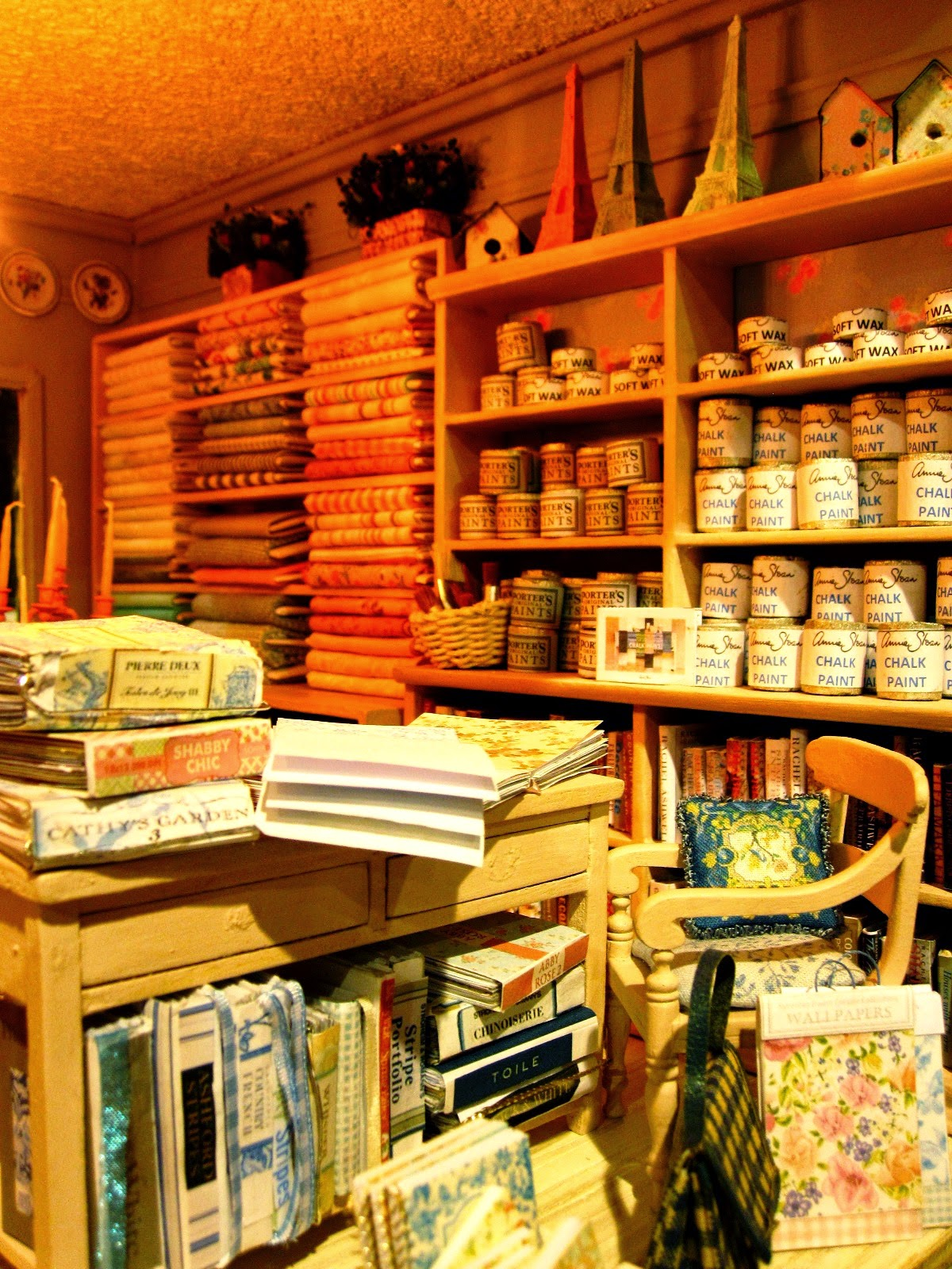 The right-hand side of a modern miniature shabby chic shop, showing wallpaper sample books, and shelves full of fabric and paint tins.