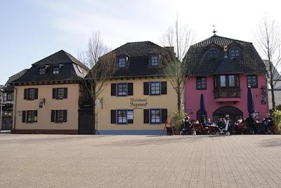 Zwei gelbe und ein Magentafarbenes Haus mit braunen Ziegeldächern. Vor dem rechten, magentafarbenen Haus sitzen Leute