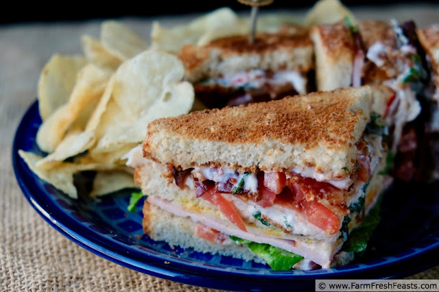 photo of  a triple bacon club sandwich with chips