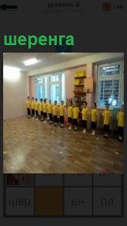 В спортивном зале стоит шеренга мальчиков в желтой спортивной форме