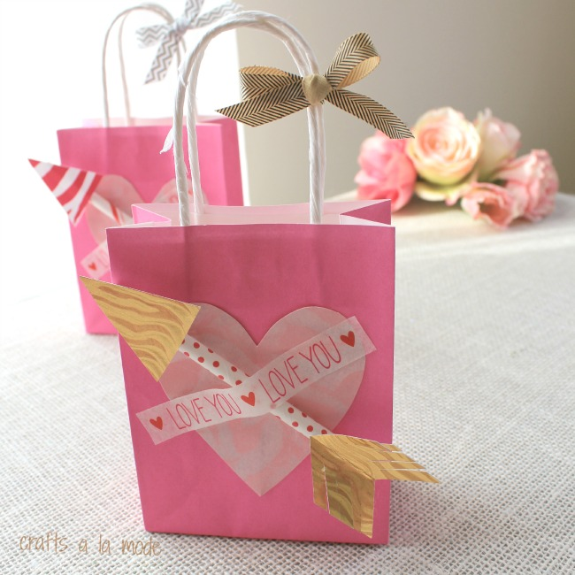 Hot pink gift bag with a handle and little arrows