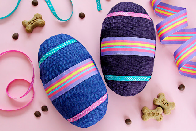 Homemade Easter egg dog toys with brightly coloured ribbons and dog treats