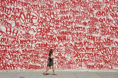 Foto de mujer pasando delante de una pared llena de pintadas o tags