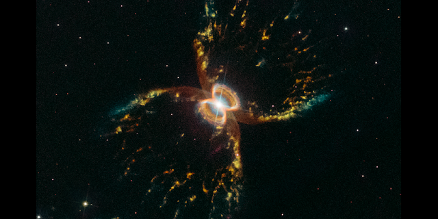 This Hubble image shows the results of two stellar companions in a gravitational waltz, several thousand light-years from Earth in the southern constellation Centaurus. The stellar duo, consisting of a red giant and white dwarf, are too close together to see individually in this view. But the consequences of their whirling about each other are two vast shells of gas expanding into space like a runaway hot air balloon. Both stars are embedded in a flat disk of hot material that constricts the outflowing gas so that it only escapes away above and below the stars. This apparently happens in episodes because the nebula has two distinct nested hourglass-shaped structures. The bubbles of gas and dust appear brightest at the edges, giving the illusion of crab legs. The rich colors correspond to glowing hydrogen, sulfur, nitrogen, and oxygen. This image was taken to celebrate Hubble's 29th anniversary since its launch on April 24, 1990. Credit: NASA, ESA, and STScI