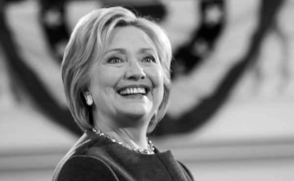 black and white image of Hillary Clinton smiling broadly at a campaign event