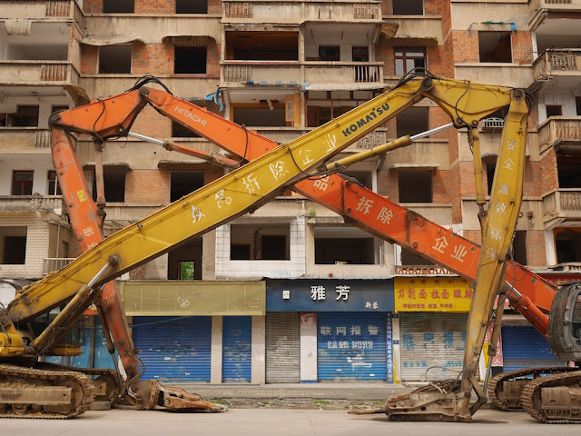 two large construction vehicles parked forming a symmetrical pattern with their arms