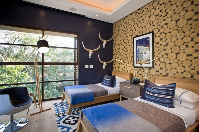 Bedroom with two beds, lamp and a single chair in Contemporary South African SGNW House by Metropole Architects