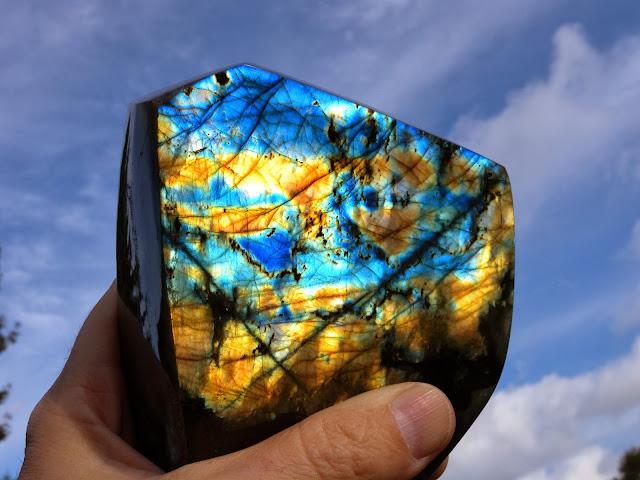 mano sosteniendo piedra labradorita teniendo como fondo el cielo azul