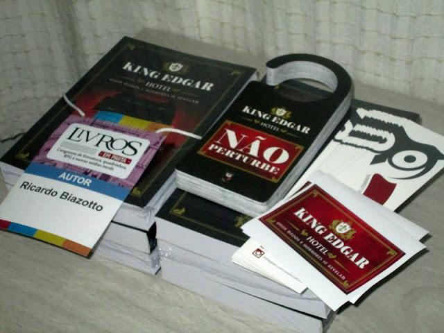 Livros e crachá do Livros em Pauta