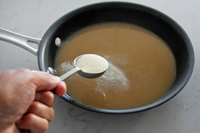 Adding gelatin powder to a pan of cool bone broth to make gummies