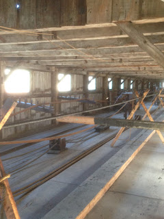 The inside of a wooden building, with wooden and metal machinery, sunlight coming in through the windows.