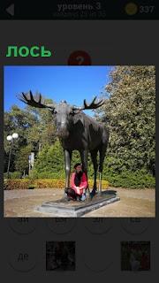 В парке размещена скульптура лося с крупными рогами и сидит мужчина