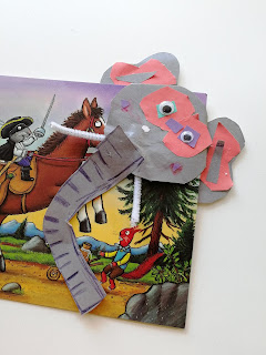 Eleanor's elephant bookmark. It's a corner bookmark, in grey, wth a long curvy trunk, pipe cleaner tusks, googly eyes and big grey ears. There are pink pieces of paper acting as the inner ear and behind the eyes. It's tucked over the edge of a Highway Rat postcard