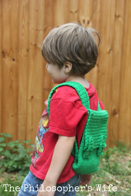 This is a side view of the little boy in a red shirt with a green backpack.  He is ready for an adventure!