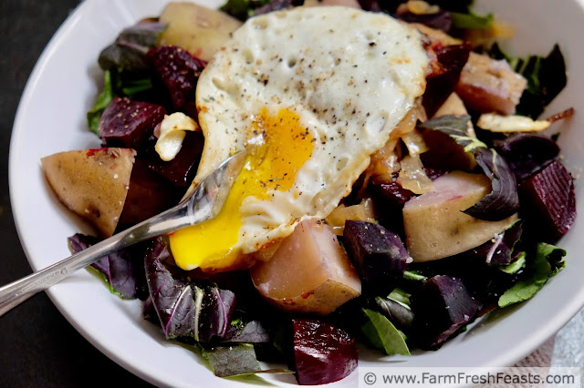 Image of a bowl of chopped bok choy topped with roasted potatoes & beets and a fried egg with runny yolk