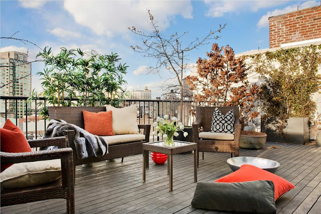 Balcony for a Soho Condo in New York City with wicker chairs and table and orange and grey accent pillows