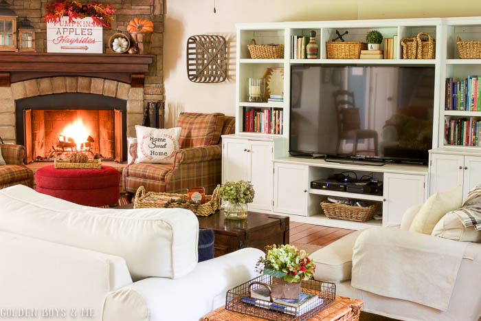 Fall family room with stone fireplace, wall unit and white slipcovered Ikea sofa and chair