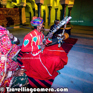 One of the exciting activity during our Churu trip was the beautiful evening when a bhopa family narrated the story of Pabuji, the Rathor Rajput Chief through their local musical instruments and songs describing the story. It was our last evening at Churu and next day we had to drive back to Delhi. The evening was full of fun with some of the awesome folk songs along with the popular lyrics like - 'Kesariya'. This Photo Journey shares some of the moments spent listening to 'Pabuji ki Phad' and dance moments with the family, who were telling this story.Deepak the owner of Malji Ka Kamara gave us some background about Pabuji Ki Phad - From where it started, who tell this story, what all instruments they use and various other things as the evening progressed.'Pabuji Ki Phad' is a basically a religious painting, which is mainly used for telling a musical story of Pabuji. Pabuji is considered as the Rathod Rajput chief. Bhopas of Pabusar are considered as traditional narrators of this art form. This art of telling story of Pabuji is very popular in Indian state of Rajasthan and it seems that there are very few folks in the world who know about this story. and there are only handful of folks, who know the complete story of Pabuji. Pabuji is also known as 'the Ascetic Deity of Sand Desert'. More about 'Pabuji Ki Phad' can be checked at - http://en.wikipedia.org/wiki/Pabuji_Ki_PhadThis family came dressed in red with all their musical instruments including a Ravan-hattha; which is made up of goat skin and camel teeth, a dhol and a metallic instrument. The man in left photograph was the leader, who was singing with Ravan-hattha and his wife was singing along at relevant places. One of his cousins was on dhol and son was dancing of the songs.Many times the lead musician stood up to accompany his son in dancing on beautiful rajasthani folk songs. It was awesome to see him dancing along with singing and playing ravan hattha.It is believed that Ravanhatha is originated among the Hela civilisation of Sri Lanka in the time of King Ravana. The bowl is made of cut coconut shell, the mouth of which is covered with goat hide. The stick is made up of bamboo, which is attached to this shell. There are two main strings - one is made up of steel and the other is made up of a set of horse hair. To know more about Ravanhatha, check out - http://en.wikipedia.org/wiki/Ravanahatha .Not sure, how many of us could really appreciate the epic of Pabuji but for sure, everyone of us enjoyed a lot on the music showcased by this family. Almost everyone of us danced with them on floor and few of the girls made best use of this opportunity to try out all the steps used by the Rajasthani  folks at Malji Ka Kamara. Overall experience was great and thanks for Mr. Lalji who corrected many of the facts which were being presented to us during the story telling part. Usually it's difficult to complete this story in an evening and it's not even recommended. But it's a good way for making people aware about these folk arts which are there for so many years and it's good to see that some of these folks are keeping it alive. The Churu ended very well with this performance by folks of Rajasthan, India.We shall go to Churu to experience this better !