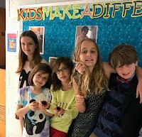 5 children lean against a bulletin board, all smiling