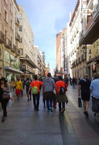 Numerosas personas transitan esta calle con sus bolsas de la compra en la mano.