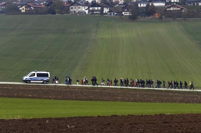 Immigrants escorted by German police to a registration camp.