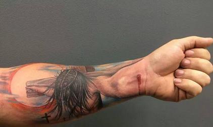 Tatuaje Jesús crucificado en el antebrazo