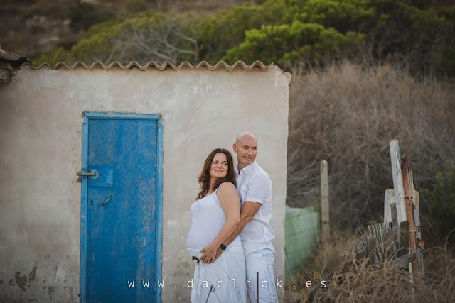 pareja embarazada frente una casa antigua