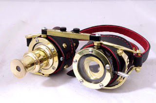 Steampunk goggles with telescopic lens in one eye (telescope) and camera aperture shutter lens in the other. Made of brass and leather.