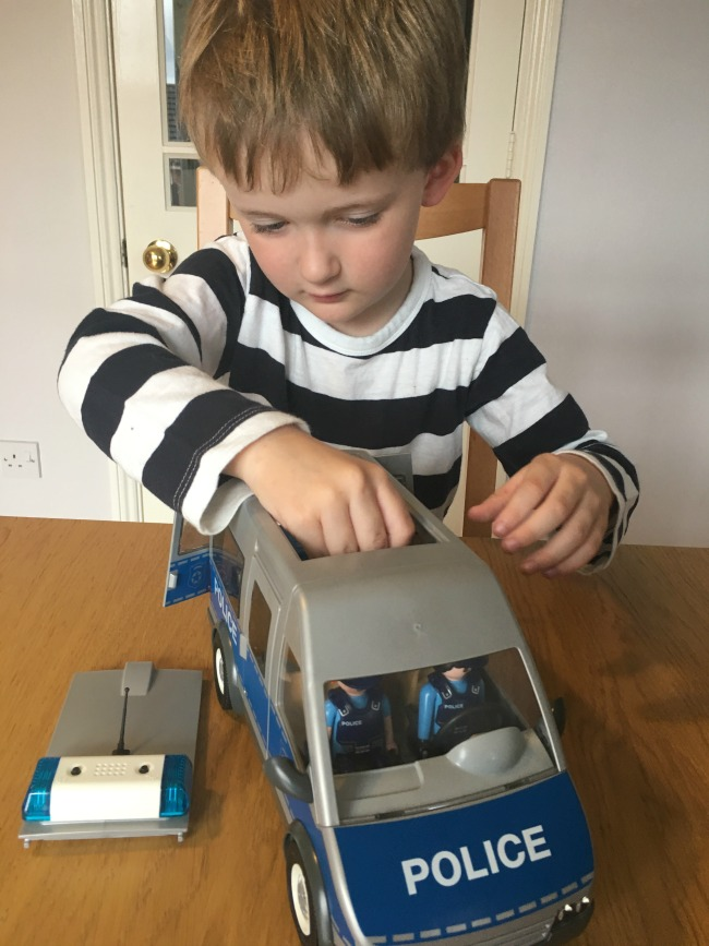 Christmas-gift-guide-2018-boy-with-playmobil-police-van-putting-figures-into-the-van-through-the-roof