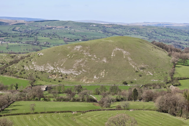 A small, rotund hill at the base of Pendle Hill with exposed limestone scars on its otherwise smooth green surface.