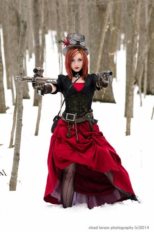 Woman dressed as a Steampunk Vampire Hunter, in the forest in the snow. Red dress, belt with weapons, guns, top hat, goggles, stockings and underbust corset. Christmas red dress, winter steampunk scene.
