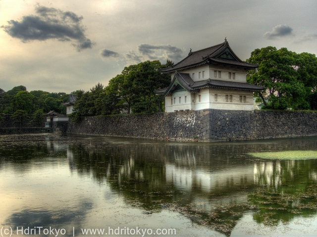 a Japanese castle turret on the stone wall. the turret reflect on the water of the moat.