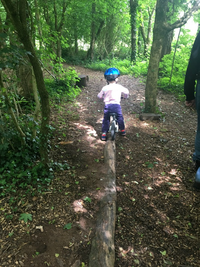 toddler-riding-a-bike-along-a-log-in-a-wood-at-tredegar-Park