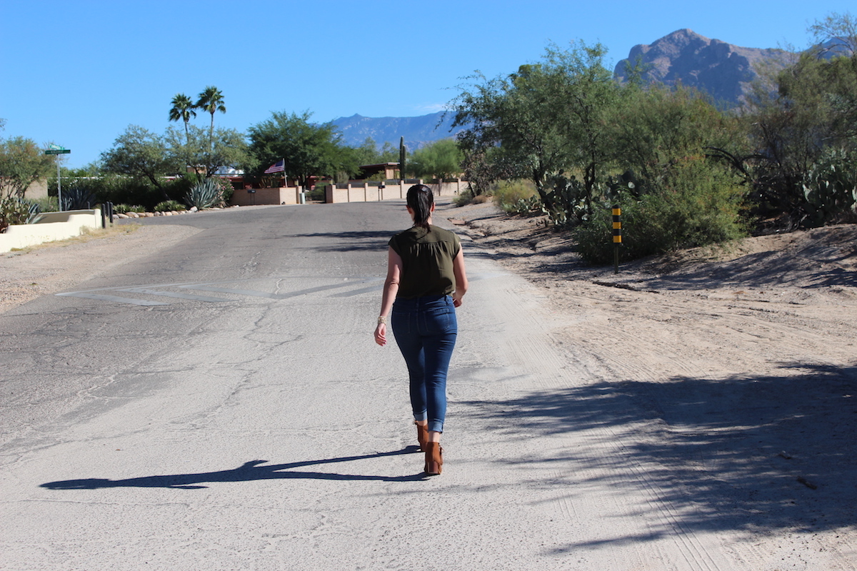 I am walking away from the camera towards the mountains, wearing an olive silk blouse, blue jeans and cognac heeled booties.