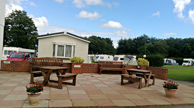 The picnic area at Forest Glade Holiday Park with caravans beyond.