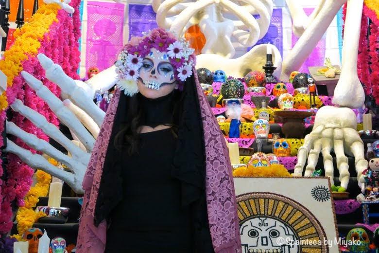 死者を祝う祭壇と花飾りを頭につけた美しい骸骨姿の女性