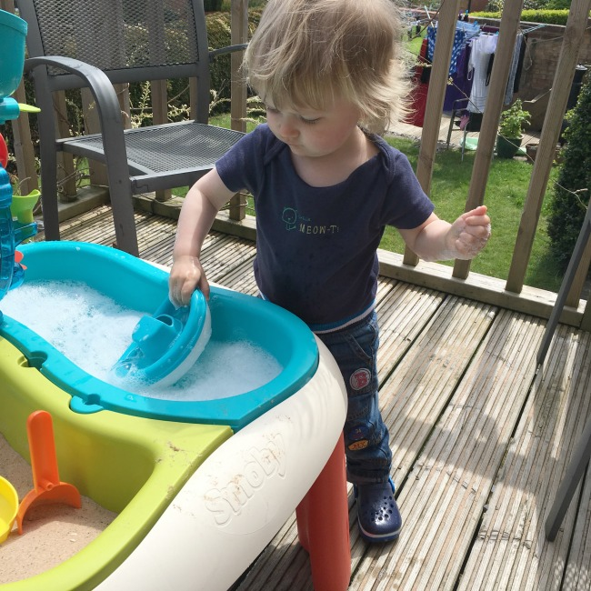 toddler with plastic boat and soapy water