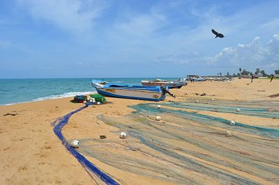 Botes y redes de pesca en la playa. A lo lejos, se ven varios pescadores en la orilla preparando sus elementos para pescar
