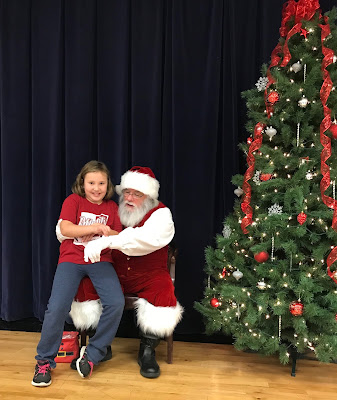 Santa sitting on a chair, on a stage, next to a Christmas Tree with a excited child on his lap