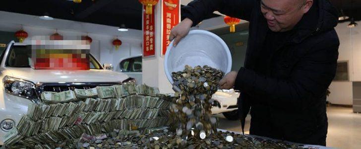 بالصور| صيني يشتري سيارة دفع ثمنها نقداً بعملات ورقية ومعدنية صغيرة في عشرة أكياس كبيرة.. واستغرق 4 موظفون في المعرض 12 ساعة لعدها