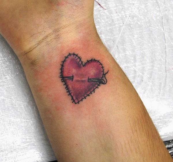 tatuaje en la muñeca de una chica de un corazón cosido de estilo infantil la aguja atraviesa el corazon tatuado