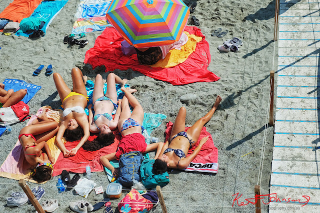 Five young women sunbaking on the beach at Monterosso Al Mare, Cinque Terre, Italy. Photographed by Kent Johnson for Street Fashion Sydney.