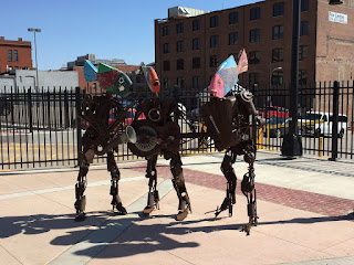 Photo of a sculpture of a band, 3 recycled metal characters with fish heads, playing saxophone, guitar, and accordion.