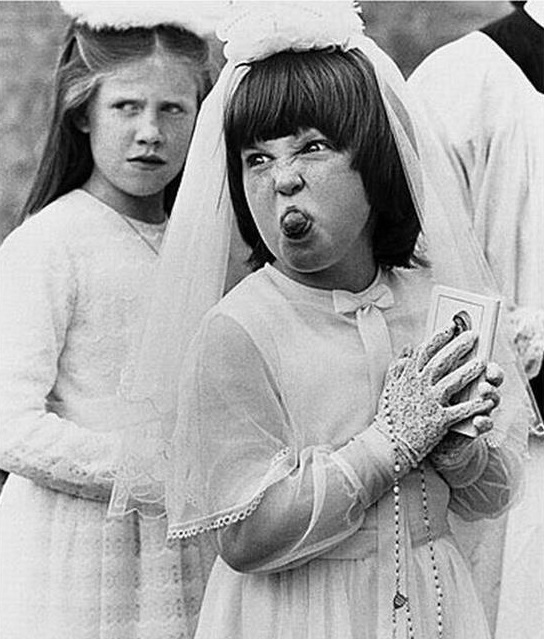 English photographer Arthur Steel. Girl at First Communion sticks her tongue out. c.1970s. The Christmas Story Explained and other stories of Christmas Creepers. marchmatron.com