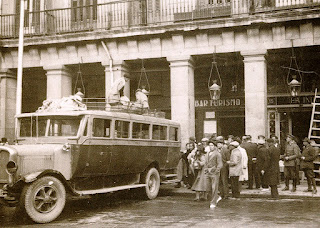 Un grupo de personas en un lateral de la plaza junto a un vehículo de transporte de viajeros.